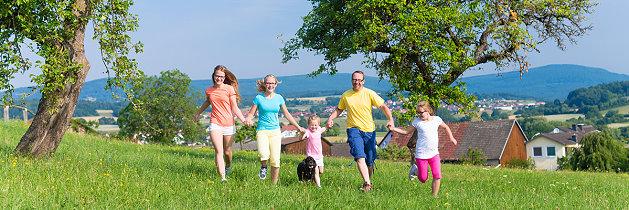 Familie rennt über eine Wiese