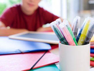 Junge mit Schulmaterialien zum Schulstart
