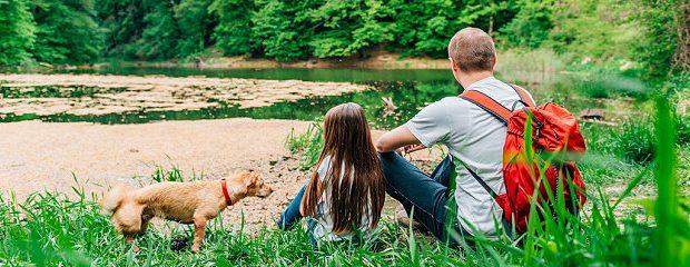 Vater, Tochter und Hund am See