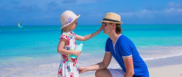 Vater und Tochter cremen sich am Strand ein