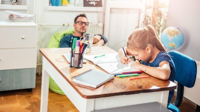 Kind macht Hausaufgaben mit Papa