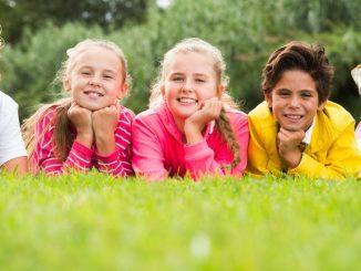 Kinder liegen auf einer Wiese und freuen sich über die Sommerferien