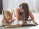 Mutter und Tochter schauen sich zum Welttag der Schulfreunde ein Fotoalbum an