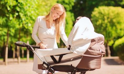 Mutter beim Spaziergang mit Kinderwagen