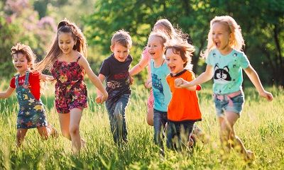 Kinder laufen glücklich über eine Wiese