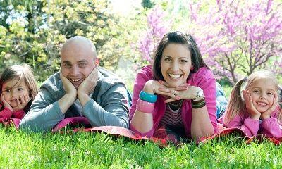 Eltern und Kinder liegen glücklich auf der Wiese